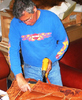 Photo of ernie apodaca installing leather over chair frame.
